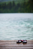Flip flops on a Dock in front of a Turquoise Water Lake Stock Images