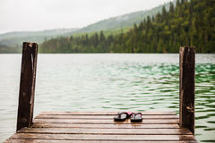 Flip flops on a Dock in front of a Turquoise Water Lake Stock Image