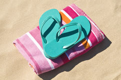 Flip-flops e toalha na praia. Imagens de Stock