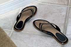 Flip flops on floor. A pair of woman's black and woven flip flops on a tile floor Royalty Free Stock Images