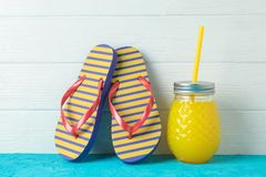 Flip flops and glass jar with fresh juice on color table against white wooden background, space for text. Summer vacation stock photos