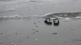 Flip flops on gray-yellow sandy beach near sea waves. vacation concept stock video
