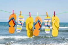 Flip-flops hanging on a clothes line. Closeup of some different pairs of colorful flip-flops hanging on a clothes line on the beach, with the sea in te royalty free stock photo