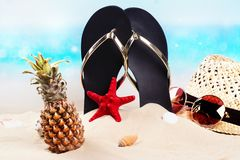 Beach flip flops, hat and sunglasses on the beautiful sandy beach near the ocean. Copy space royalty free stock photography