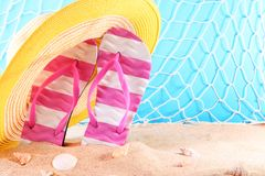 Flip flops with hat and seashells. Flip flops with yellow hat and seashells on the beach sand royalty free stock image