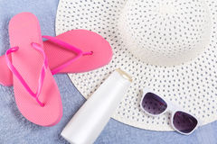 Flip flops, hat, sunglasses over blue towel Stock Photo