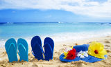Flip flops and hat with tropical flowers on sandy beach Royalty Free Stock Photos