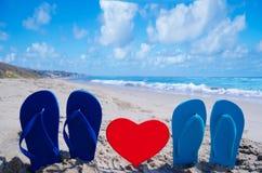 Flip flops with heart on the beach Stock Photos