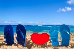 Flip flops with heart shape on the sandy beach Royalty Free Stock Images