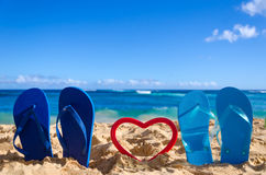 Flip flops with heart shape on the sandy beach Stock Image