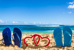 Flip flops with heart shapes on the sandy beach Stock Image