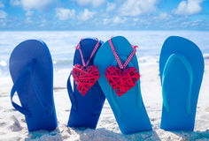 Flip flops with hearts on the beach. Flip flops with two heart shapes on the sandy beach by the ocean stock photography