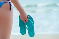 Flip Flops In The Hand Of A Girl On The Beach Royalty Free Stock Photography