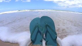 Flip Flops Knocked Over. Wave washes in and knocks over a pair of flip flops stuck in the sand on the beach stock video