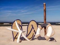 Flip-flops, life buoy and starfish on the beach Stock Photos