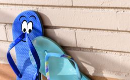 On flip flops a man and a woman show their love on a brick wall Royalty Free Stock Images