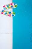 Flip-flops near the swimming-pool. Two flip-flops with flowers near the swimming-pool in the morning sun Stock Photos
