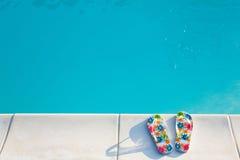 Flip-flops near the swimming-pool. Two flip-flops with flowers near the swimming-pool in the morning sun Stock Image