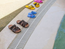 Flip flops near a swimming pool Stock Images