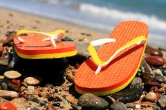 Flip-flops. Orange flip-flops on the beach in Barcelona royalty free stock photo