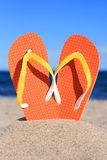 Flip-flops. Orange flip-flops in sand on the beach in Barcelona royalty free stock image