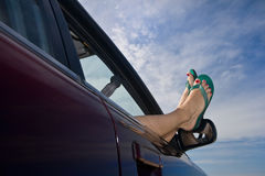 Flip Flops Out The Car Window. Woman's legs with bright green flip-flops (sandals) dangling out a car window parked at the beach Stock Images