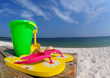 Flip flops and pail on boardwalk. Colorful flipflops, beach pail, and shells on boardwalk by ocean stock photo
