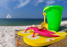 Flip flops and pail on boardwalk. Colorful flipflops, beach pail, and shells on boardwalk by ocean stock images