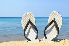 Flip flops. A pair of flip flops stuck in sand on the beach stock photos