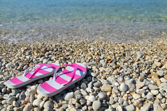 Flip flops on pebbled beach closeup Stock Images
