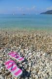 Flip flops on pebbled beach Stock Photography
