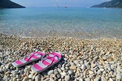 Flip flops on pebbled beach Royalty Free Stock Photo