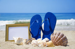Flip-flops with photoframe and seashells on beach. Flip-flops with photoframe and seashells on sandy beach Stock Photography