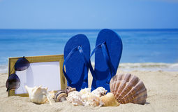 Flip-flops with photoframe and seashells on sandy beach Stock Photos