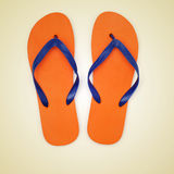 Flip-flops. Picture of orange and blue flip-flops on a beige background, with a retro effect stock image