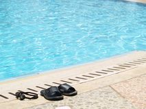 Flip-flops at the pool. Slippers and goggles at the side of the pool Royalty Free Stock Photos