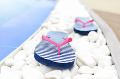 Flip flops at the pool on pebbles. royalty free stock images