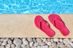 Flip flops by the poolside with water Stock Images