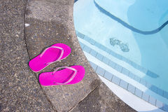 Flip flops at private pool side Stock Photo