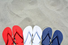 Flip flops. Red white and blue flip flop sandals on the sand, plenty of room for your text Royalty Free Stock Photography