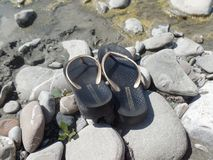 Flip flops on the river bed. Flip flops perched on grey stones on the river bed royalty free stock photography