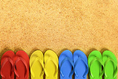 Flip flops in a row, beach sand background, copy space Stock Photo