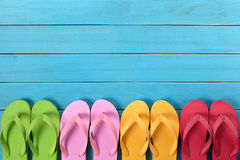 Flip flops in a row with blue beach deck background, copy space royalty free stock photography