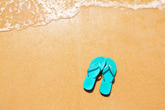 Flip flops on the sand. Flip flops on a sandy ocean beach royalty free stock images