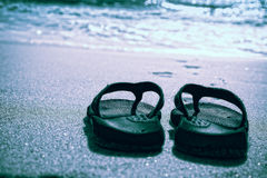 Flip flops on a sand beach Stock Images