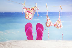 Flip flops in sand and bikinis hanging on tropical beach Stock Image