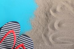 Flip-flops in the sand on a blue background. Top view royalty free stock images
