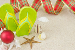 Flip Flops in the sand and Christmas decoration. Flip Flops in the sand with shells and Christmas decoration. Xmas summertime on beach concept royalty free stock photography