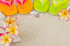 Flip Flops in the sand with shells and flowers Royalty Free Stock Photos