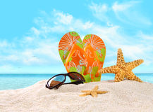 Flip- flops in the sand with starfish. Pair of flip- flops in the sand with starfish royalty free stock photography